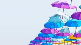 Kleurrijke paraplu's die in de lucht hangen - blauwe hemel met exemplaarruimte royalty-vrije stock afbeeldingen