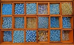 Kleurrijke parels in verschillende die grootte en vormen in houten compartiment wordt verkocht Stock Foto's