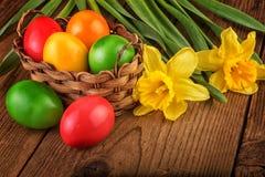 Kleurrijke Pasen-decoratie met eieren in mand op donkere houten lijst royalty-vrije stock foto's