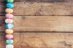 Kleurrijke pastelkleurpaaseieren op houten achtergrond met ruimte vin Stock Fotografie