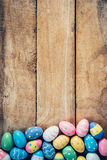 Kleurrijke pastelkleurpaaseieren op houten achtergrond met ruimte vin Stock Afbeeldingen