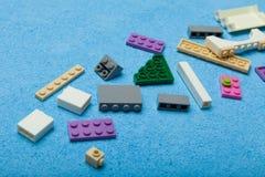 Kleurrijke plastic aannemer, stuk speelgoed details op een blauwe achtergrond Delen van heldere stukken voor bouw stock afbeeldingen