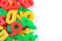 Kleurrijke plastic aantallen op wit Stock Afbeeldingen