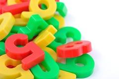 Kleurrijke plastic aantallen op wit Stock Foto