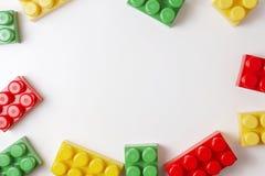 Kleurrijke plastic bouwblokken op witte achtergrond als kader van het jonge geitjesspeelgoed met exemplaarruimte voor tekst Vlak  Royalty-vrije Stock Afbeelding
