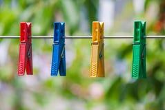 Kleurrijke plastic wasknijpers op een kabel stock afbeeldingen