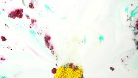 Kleurrijke poederinkt die op melk, hoogste mening stromen Sluit omhoog voor droge kleurrijke verf op oppervlakte van witte vloeis stock footage