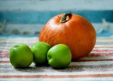 Kleurrijke pompoen en drie groene appelen op de Indische deken stock afbeeldingen