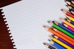 Kleurrijke potloden en leeg document op oud bureau Stock Afbeelding