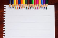 Kleurrijke potloden en leeg document op oud bureau Royalty-vrije Stock Afbeeldingen