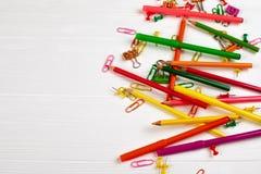 Kleurrijke potloden en viltpennen, paperclippen, kantoorbehoeftenspijkers, smilie bindmiddelen op witte houten achtergrond Stock Foto's