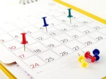 Kleurrijke punaise op belangrijke dag in kalender stock afbeelding
