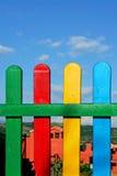 Kleurrijke rijen van geschilderd hout op een speelplaatsomheining stock afbeeldingen