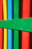 Kleurrijke rijen van geschilderd hout op een speelplaatsomheining royalty-vrije stock afbeelding