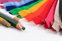 Kleurrijke ritssluitingen en potloden witte achtergrond Stock Fotografie