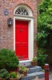 Kleurrijke rode deur en bakstenen muur Stock Foto