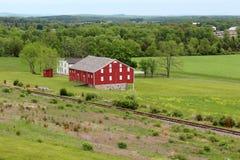 Kleurrijke rode schuur en boerderij in platteland Stock Foto