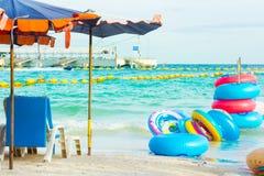 Kleurrijke rubberringen en ligstoelen bij het strand stock foto