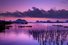 Kleurrijke schemering in ochtend over zeegezicht bij vissersdorp, Stock Afbeelding