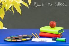 Kleurrijke schoolbehoeften en twee boeken op donkerblauwe lijst opnieuw royalty-vrije stock foto
