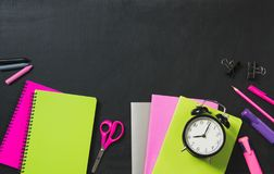 Kleurrijke schoollevering, groen, roze, voorbeeldenboek en wekker op zwart bord De hoogste vlakke mening, legt, kopieert ruimte Stock Afbeelding