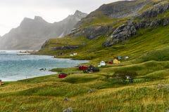 Kleurrijke Skandinavische huizen bij een mooie die baai door bergen en een klein dorp dichtbij Bunes-Strand wordt omringd en Vins royalty-vrije stock afbeelding