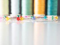 Kleurrijke spelden met een achtergrond van naaiende draad royalty-vrije stock foto