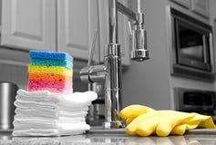 Kleurrijke sponsen en handschoenen in keuken Stock Fotografie