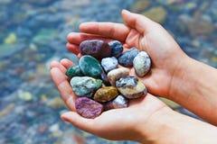 Kleurrijke stenen in handen Stock Afbeelding