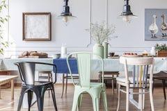 Kleurrijke stoelen bij lijst in eclectisch grijs eetkamerbinnenland met lampen en bloemen Echte foto stock foto