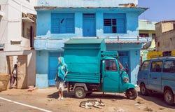 Kleurrijke straat met traditionele huizen van blauwe kleuren en dame die zich dichtbij oude vrachtwagen bevinden Stock Fotografie