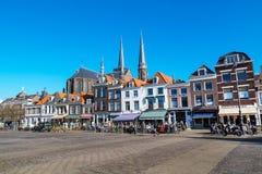 Kleurrijke straatmening met huizen en mensen in Delft, Holland Stock Foto's