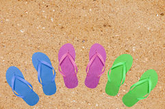 Kleurrijke strandschoenen op geel zand Stock Afbeeldingen