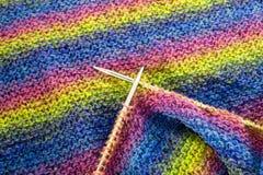Kleurrijke strepen gebreide wol met naalden achtergrondtextuurclose-up Stock Afbeeldingen