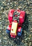 Kleurrijke stuk speelgoed tractor en kiezelstenen in het water Royalty-vrije Stock Fotografie