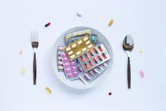 Kleurrijke tabletten, capsules en pillen met witte schotel, mensen en lepel op wit stock foto