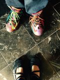 Kleurrijke tennisschoenen en zwarte schoenen Royalty-vrije Stock Foto's
