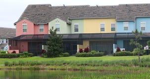 Kleurrijke terrasvormige huizen met zwembad en meermening stock videobeelden