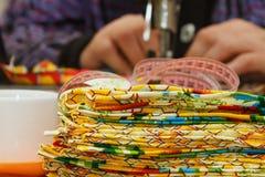 Kleurrijke textiel en handnaaisters op de achtergrond Stock Afbeelding