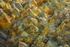 Kleurrijke textuur van vulkanische rots op de Achtergrond stock foto
