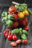 Kleurrijke tomaten in een mand en op houten achtergrond Stock Afbeeldingen