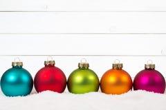 Kleurrijke van Achtergrond Kerstmisballen op een rij houten decoratiesno Stock Afbeeldingen