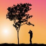 Kleurrijke vector met een mens die vogels fotograferen die op een boom zitten royalty-vrije illustratie