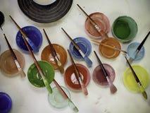 Kleurrijke verfblikken en borstels in atelier Stock Foto's