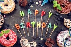 Kleurrijke verjaardagsachtergrond met donuts en cupcakes op donkere bedelaars Royalty-vrije Stock Foto