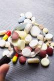 Kleurrijke verschillende capsules en pillen onder vergrootglas op grijze achtergrond Stock Afbeeldingen