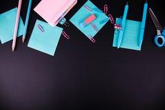 Kleurrijke verschillende kantoorbehoeften op een zwarte achtergrond stock afbeelding