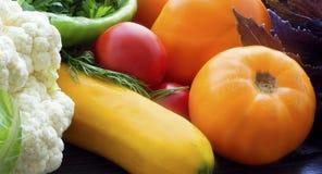 Kleurrijke verse groentenachtergrond Rijpe groentenclose-up Tomaten, bloemkool, courgette, hete peper en kruiden stock fotografie