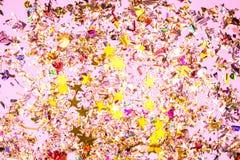 Kleurrijke vieringsachtergrond met confettien, sterren, vuurwerk en decoratie op roze achtergrond stock foto's