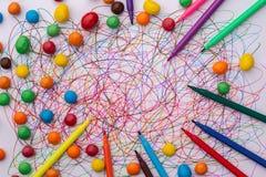 Kleurrijke vilten uiteindepen met snoepjes en gekrabbel op Witboek stock fotografie
